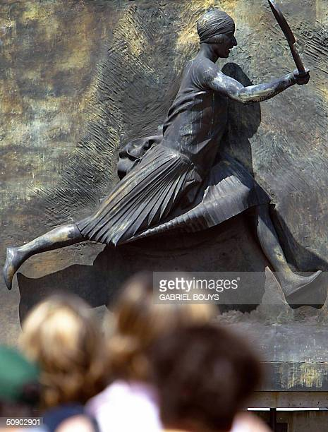 People stand infront of the statue of late French player Suzanne Lenglen during the French tennis open at Roland Garros in Paris 27 May 2004 AFP...