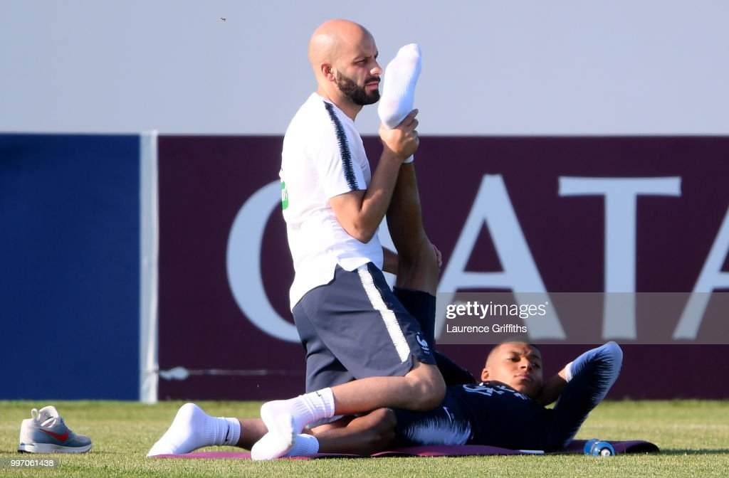 France physiotherapist Guillaume Vassout helps Kylian Mbappe in the stretching execises during a France trainig session on July 12, 2018 in Moscow, Russia.
