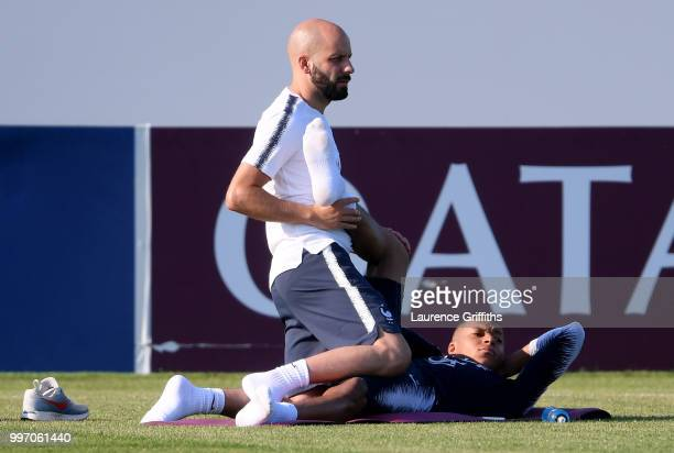 France physiotherapist Guillaume Vassout helps Kylian Mbappe in the stretching execises during a France trainig session on July 12 2018 in Moscow...