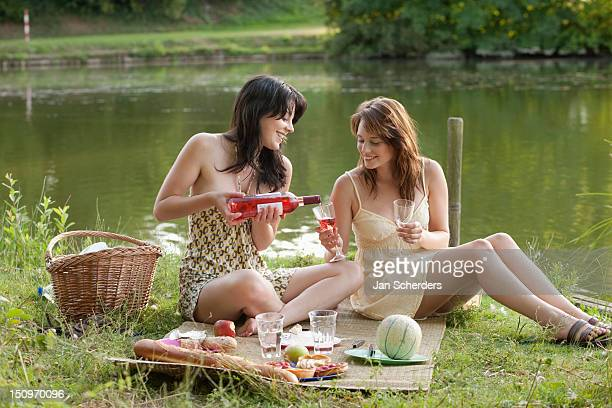 France, Picardie, Albert, Young women having picnic on lakeside