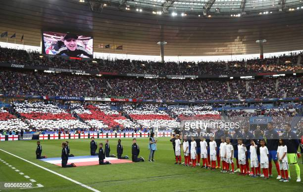 France players line up as an England flag is displayed by the fans prior to the International Friendly match between France and England at Stade de...