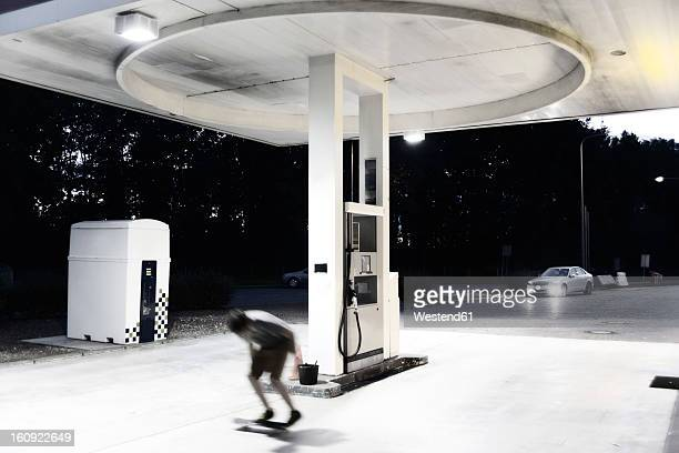 France, Poitiers, Teenage boy skating on petrol station