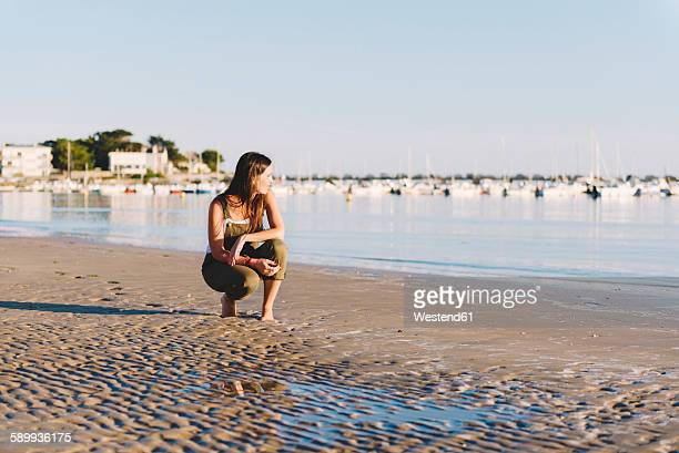 France, Pornichet, woman crouching on the beach at sunset