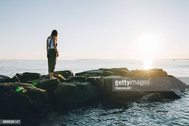 France, Pornichet, woman standing on rocks at seafront by sunset