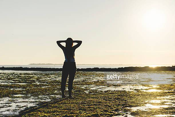 France, Pornichet, woman with hands behind the head standing on the beach looking at sunset