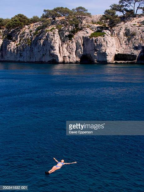 france, provence, cassis, calanques, woman floating in mediterranean - calanques stock pictures, royalty-free photos & images