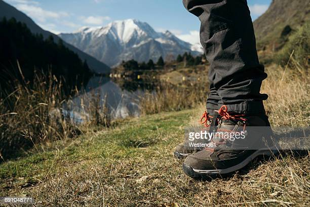 France, Pyrenees, Pic Carlit, close-up of hiker taking a rest at mountain lake