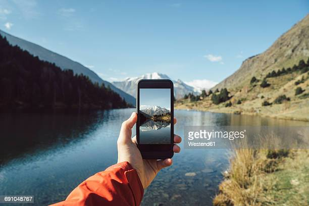 France, Pyrenees, Pic Carlit, man taking a picture at mountain lake