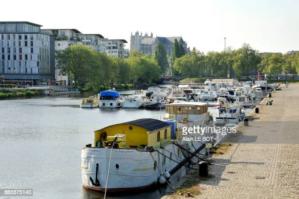 France, region of Pays de La Loire, Loire-Atlantique department, Nantes city, boats moored on canal of Saint-Felix, Cathedral of St. Peter and St. Paul in the back.