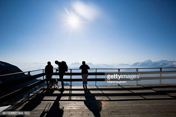france, rhone-alpes, isere, alpe d'huez, silhouettes of three people on top of pic blanc mountain - observation point stock pictures, royalty-free photos & images