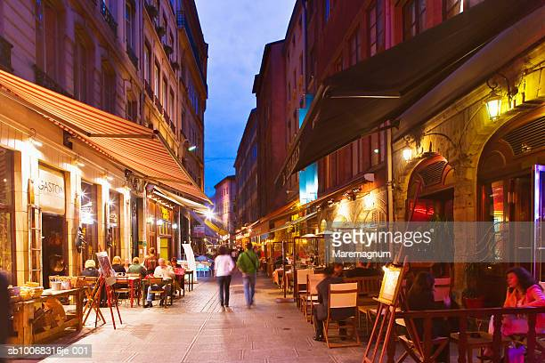 France, Rhone-Alpes, Lyon, Illuminated restaurants along Merciere street at dusk