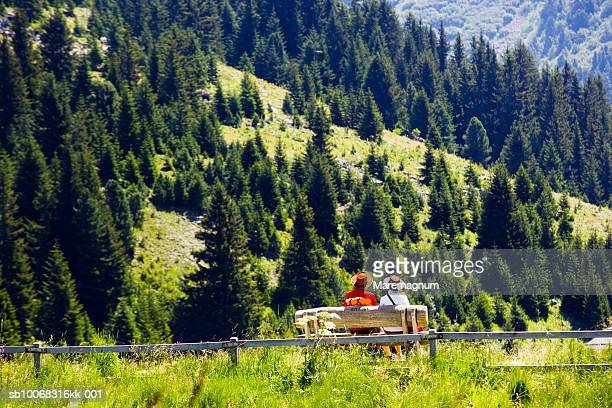 france, rhone-alpes, savoy, les allues, meribel-mottaret, tourists on bench overlooking forest, rear view - eco tourism stock pictures, royalty-free photos & images