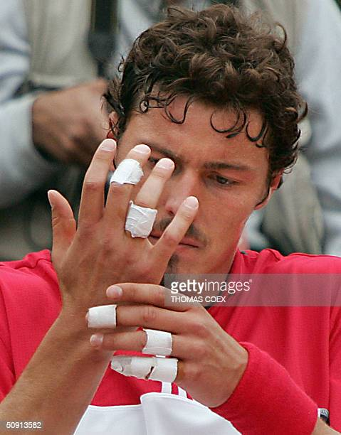Russian Marat Safin looks at his blisters during his match against Argentinean David Nalbandian in the fourth round of the French Open at Roland...