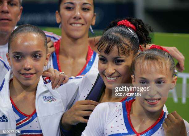 France 's gymnasts Camille Schmutz Isabelle Severino Soraya Chaouch and Emilie Le Pennec pose together 15 August 2004 at the Olympic Indoor Hall...