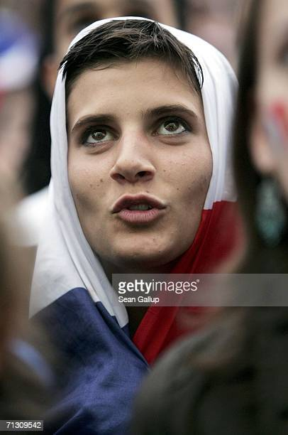 France soccer fan covered in a French flag reacts to play during their FIFA World Cup 2006 Round of 16 match against Spain at an open-air public...