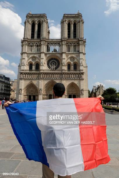 A France supporter holds a French flag in front of NotreDame Cathedral prior to the start of the Russia 2018 World Cup final football match between...