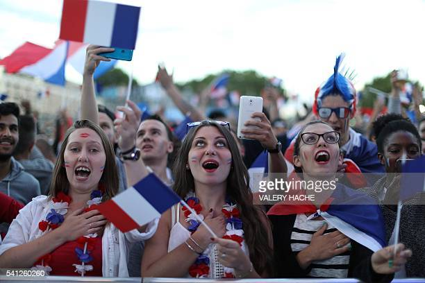 TOPSHOT France supporters sing the French national anthem as they watch the Euro 2016 group A football match between Switzerland and France in a fan...