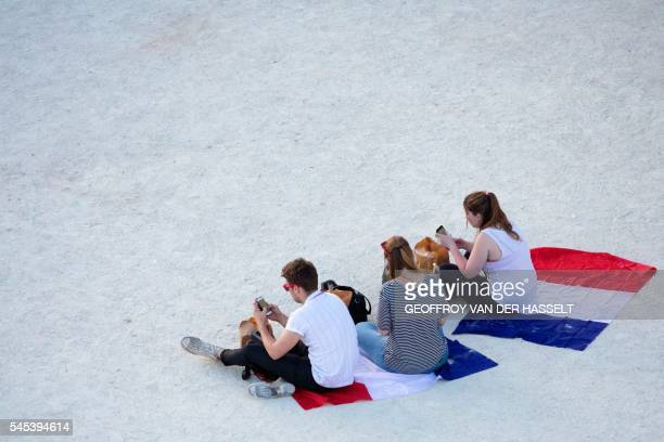 France supporters sit as they hold their phones during the Euro 2016 semifinal football match between Germany and France at the Paris Champs de Mars...