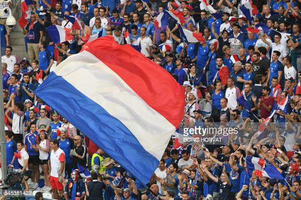France supporters wave the national flag ahead the Euro 2016 semifinal football match between Germany and France at the Stade Velodrome in Marseille...