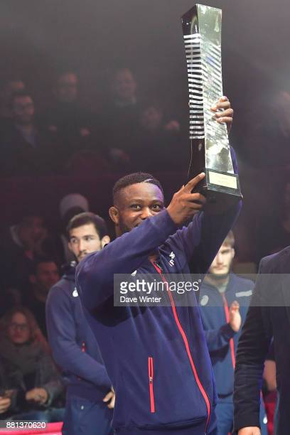 France team captain Melonin Noumonvi of France holds up the winning team trophy following during the International wrestling test match between...