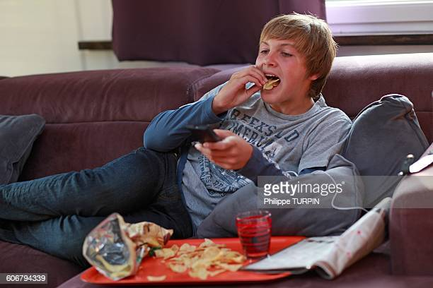 france teenager eating and watching tv - ready to eat stock pictures, royalty-free photos & images