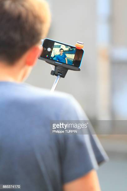 France, teenager using telescopic pole to film himself or photograph himselph.