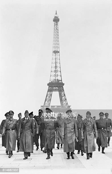 France: The famous Eiffel Tower, symbol of the city of Paris, is pictured in the background as Hitler and his party go sightseeing through the...