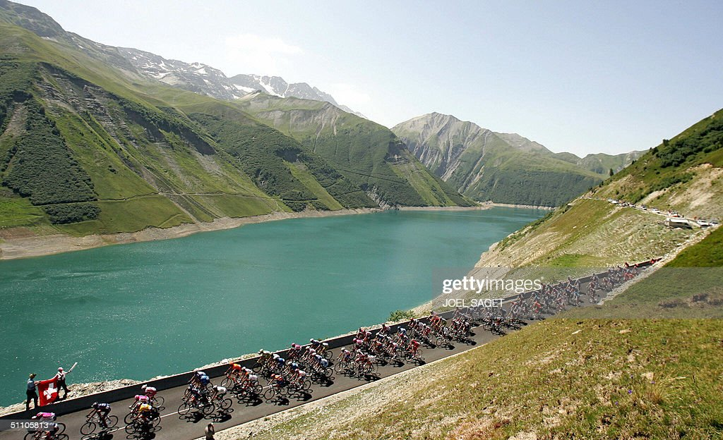 The pack ride by a lake as two persons wave a flag from Savoie during the 17th stage of the 91st Tour de France cycling race between Bourg-d'Oisans and Le Grand Bornand, 22 July 2004.