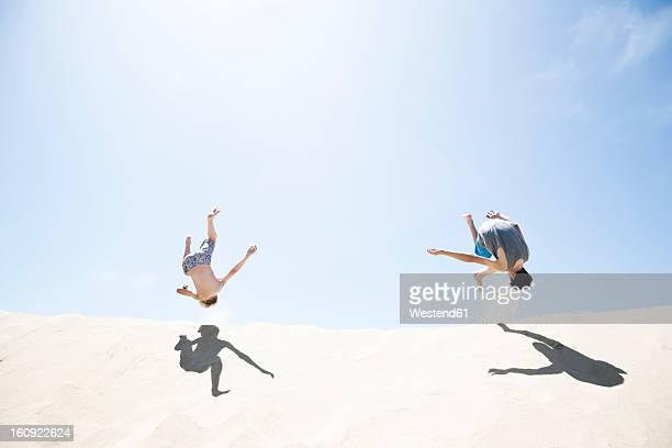 France, Two Boys jumping on sand dune