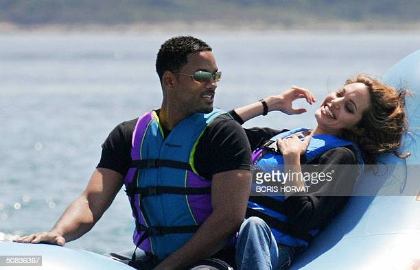US actor Will Smith and actress Angelina Jolie ride a promo float during a photo call at the Carlton Hotel beach for the film 'Shark Tale' 14 May...