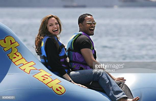 US actors Will Smith and actress Angelina Jolie ride a promo float during a photo call at the Carlton Hotel beach for the film 'Shark Tale' 14 May...
