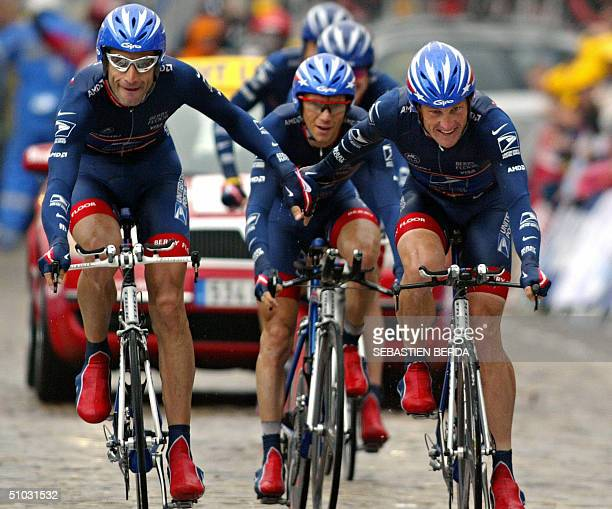 US Lance Armstrong and his teammate George Hincapie hold their hands as they arrive and win the team time trial in the fourth stage of the 91st Tour...