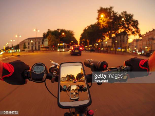 france, versailles, personal perspective of man riding e-bike on avenue de l'europe at twilight - handlebar stock pictures, royalty-free photos & images