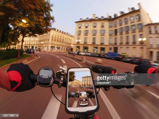 france, versailles, place hoche, personal perspective of man riding e-bike at twilight - handlebar stock photos and pictures