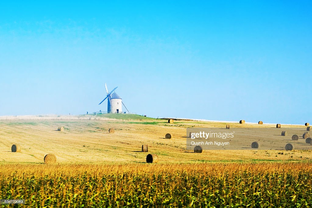 France, windmill in a harvested field : Foto de stock