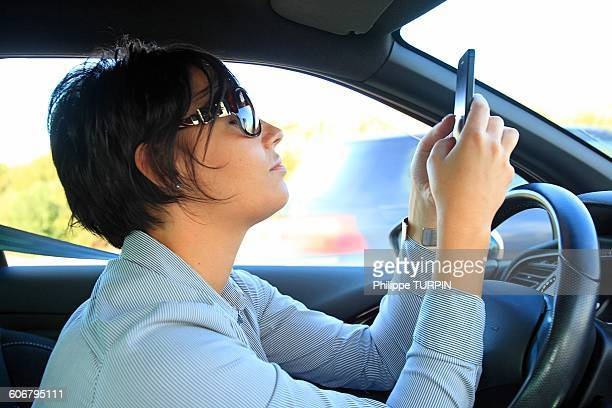 France, woman in car with phone