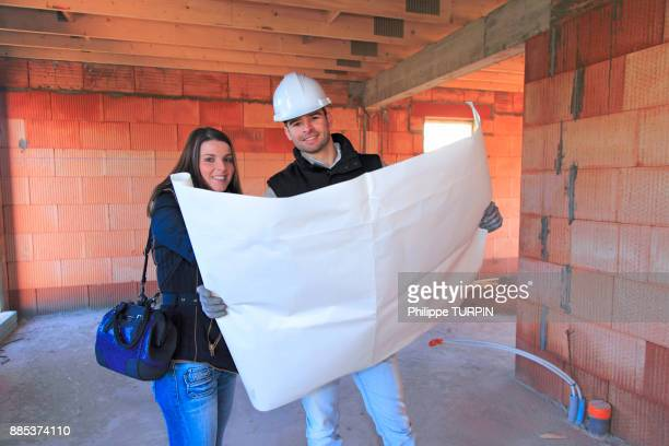 France, young architect and customer in a house in construction.