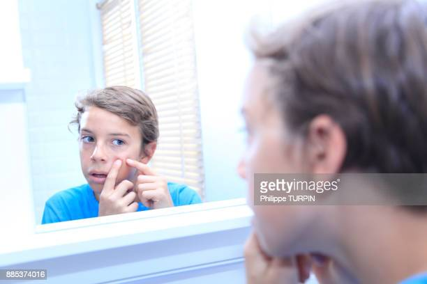 France, young boy in the bathroom looking in the mirror.