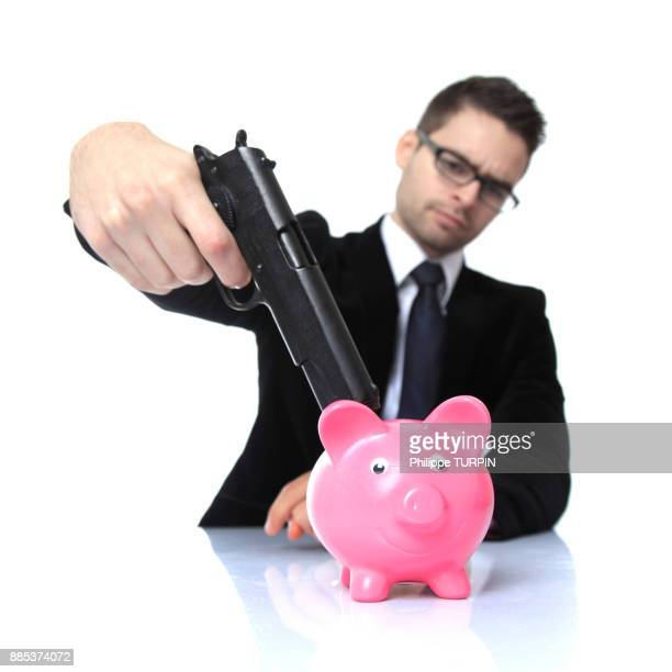 france, young man in costume with a gun, money boxe on a table in front of him. - capitalism stock pictures, royalty-free photos & images