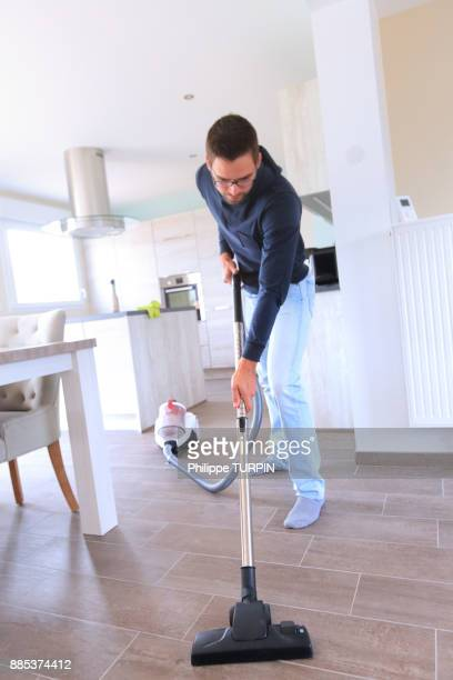 France, young man using vacuum cleaner.