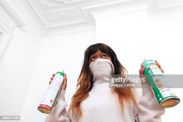 France, young woman at home with spray.