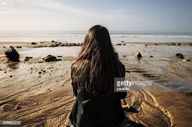 France, Young woman sitting on sand looking at sea