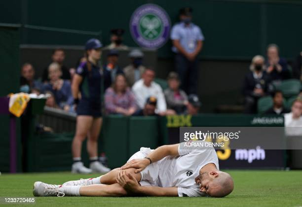 France's Adrian Mannarino holds his knee after slipping on the grass during play against Switzerland's Roger Federer during their men's singles first...