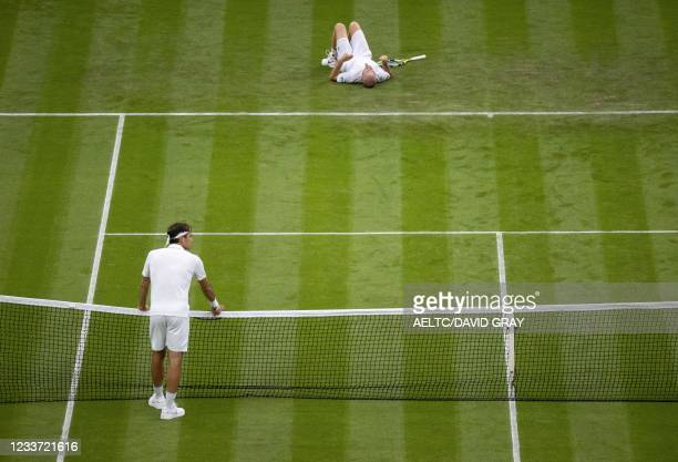 France's Adrian Mannarino lays on the court in jured after slipping while returning against Switzerland's Roger Federer during their men's singles...