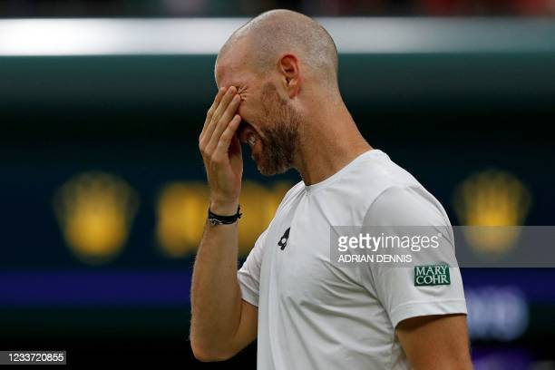 France's Adrian Mannarino reacts as he withdraws from his men's singles first round match against Switzerland's Roger Federer, on the second day of...