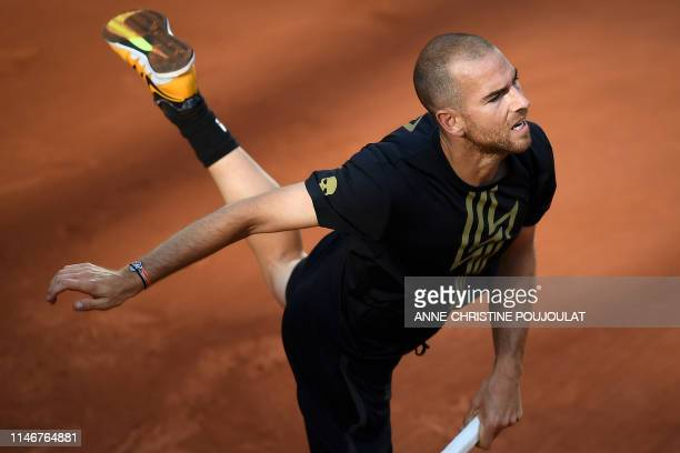 TOPSHOT France's Adrian Mannarino serves a ball to Italy's Stefano Travaglia during their men's singles first round match on day three of The Roland...