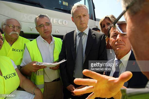 France's Agriculture minister Bruno Le Maire listens to a man next to a lorry carrying Spanish fruits at a motorway tollbooth in the French southern...