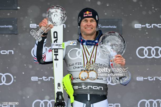 France's Alexis Pinturault poses for pictures holding the Men's Overall Cristal Globe of the FIS Alpine Ski World Cup and the Overall Cristal Globe...