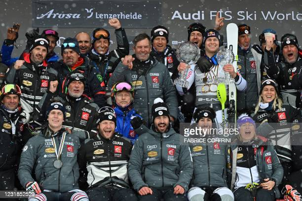 France's Alexis Pinturault poses for pictures with France's team, holding the Men's Overall Cristal Globe of the FIS Alpine Ski World Cup and the...