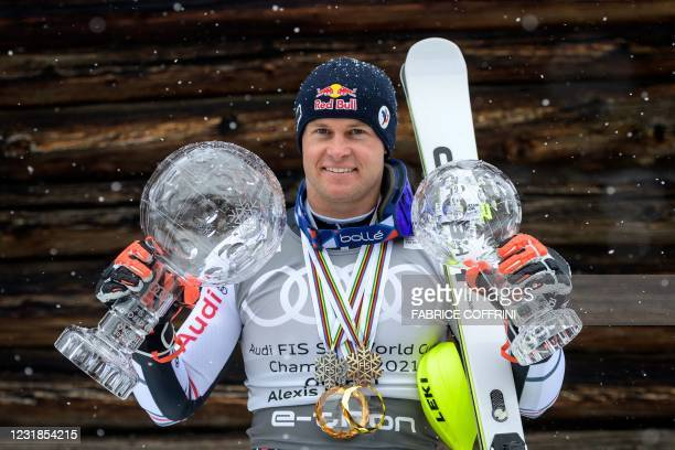 France's Alexis Pinturault poses for pictures with the Men's Overall Cristal Globe of the FIS Alpine Ski World Cup and the Overall Cristal Globe of...